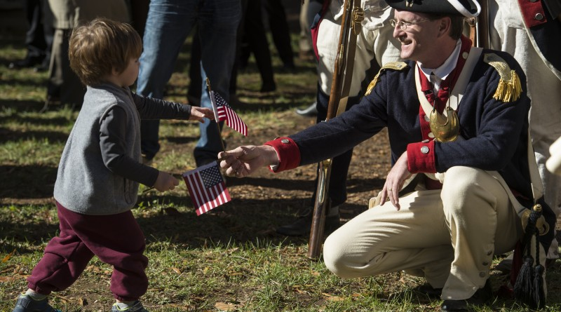 Dedication of the Revolutionary War Memorial Statue on the grounds of the Loudoun County Court House in Leesburg Virginia, November 11, 2015. Here Aiden Bohince (2) of Leesburg offers up a flag to a Revolutionary War reenactor. (Photo By Douglas Graham/Loudoun Now)