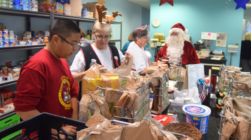 Santa helps Loudoun Interfaith Relief's group of Wednesday volunteers, known as the Nut Bunch,  page food bags.