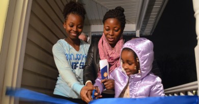 Edith, Marina and Pearl Kemoh cut a ribbon to celebrate their new home in Leesburg, purchased through the help of Loudoun Habitat for Humanity.