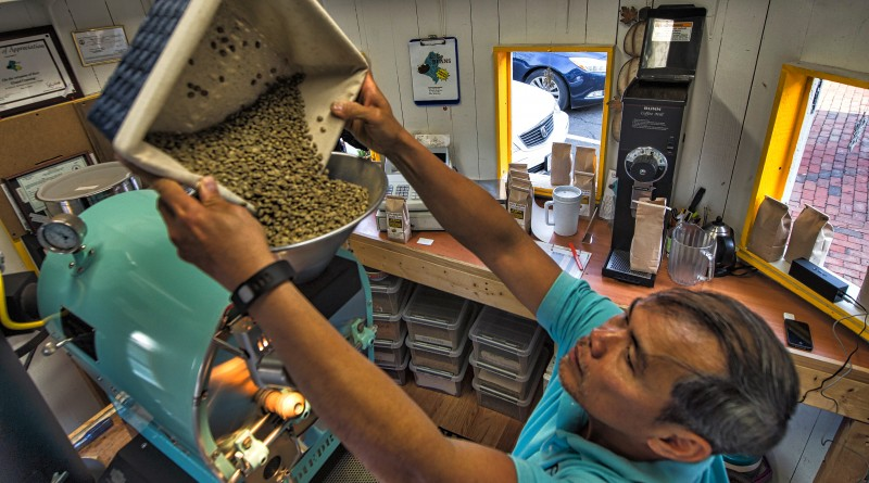 Chau Pham loads fresh beans into the roaster at LoCo Beans fresh roasted coffee located in the Silo at Market Station in Leesburg Virginia. (Photo by Douglas Graham/Loudoun Now)
