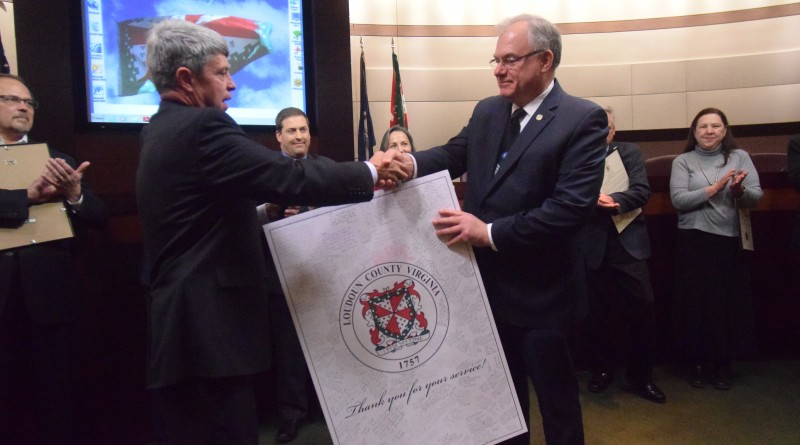 Vice Chairman Ralph M. Buona presents outgoing Chairman Scott K. York with a seal of Louduon County covered in signatures and well-wishes from county staff members.