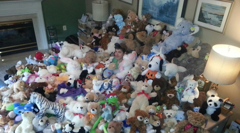 Andrew Stephenson is covered with stuffed animals that will be used to comfort children in emergency situations.