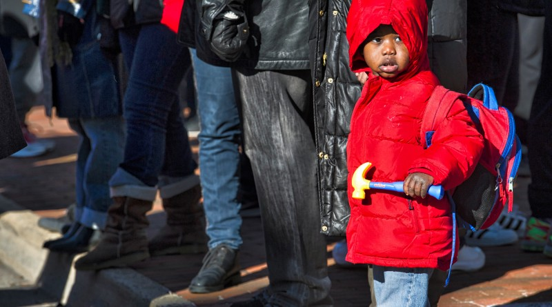 """Christian Phiri, age 3, waits at the Loudoun County Court House in downtown Leesburg before the march to Douglass Community Center for the 24th annual Martin Luther King Jr. """"I Have a Dream"""" celebration.  (Photo by Douglas Graham/Loudoun Now)"""