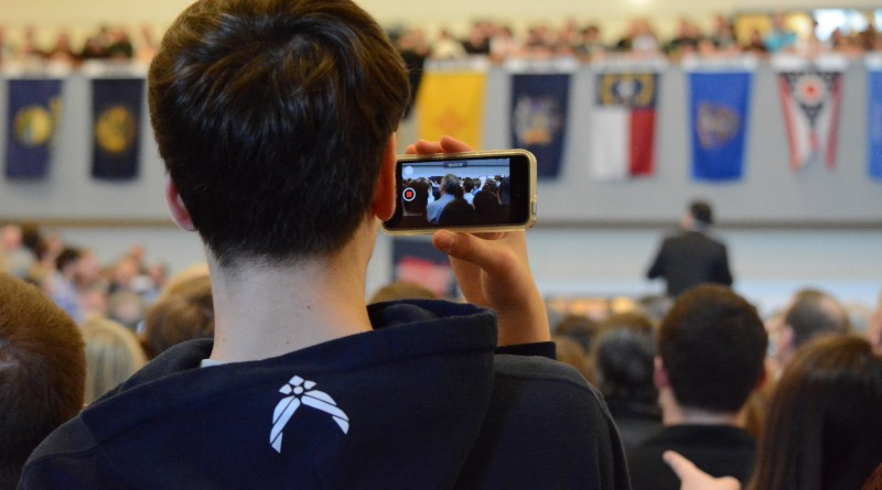 A young fan records the rally on his phone.
