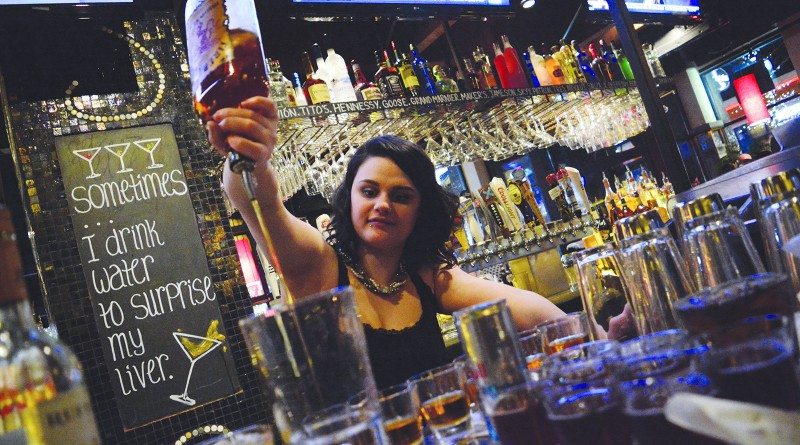 A bartender pours drinks on a busy Saturday night at Bar Louie in One Loudoun. (Renss Greene/Loudoun Now)
