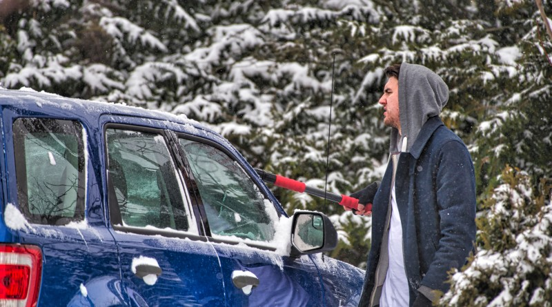 Chris Dodson clears his car of snow at LoCo Joes coffee shop after a snow storm blanketed Loudoun yet again with snow and ice.  (Photo by Douglas Graham/Loudoun Now)