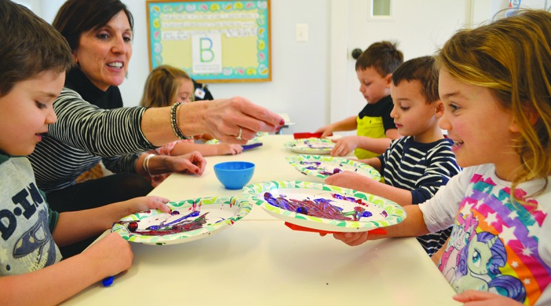 From left, student Aris Pavlopulous, teacher Cindy Backus and student Keira Bergtolio paint with magnets in a kindergarten class at Destiny School for the Arts. (Danielle Nadler/Loudoun Now)