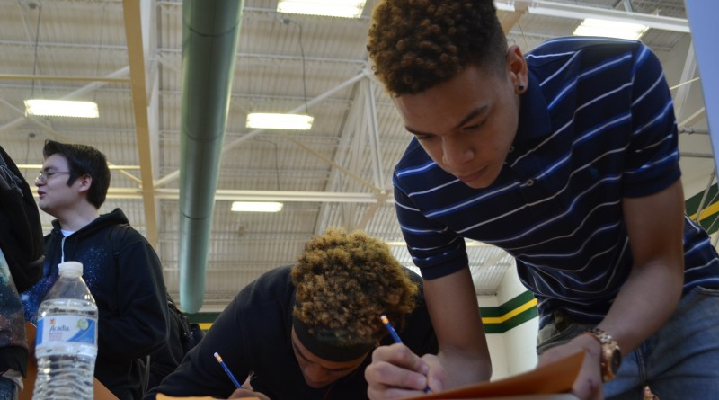 Douglass School students Tavious Lane, left, and Bryson Dolly work on their fictitious budgets as part of the Reality Store finance education event Friday. (Danielle Nadler/Loudoun Now)