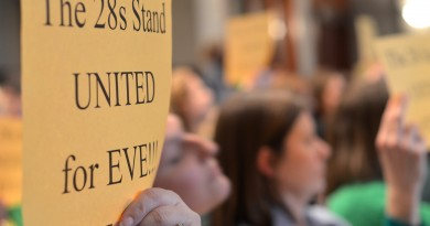 Parents of Evergreen Mill Elementary School students hold up signs referring to their attendance zone during a School Board meeting Thursday. (Danielle Nadler/Loudoun Now)