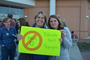 "Gretchen Falter and Anna Peach hold up a sign opposing the school board's ""Plan 12"" after the Educate Don't Segregate meeting. (Renss Greene/Loudoun Now)"