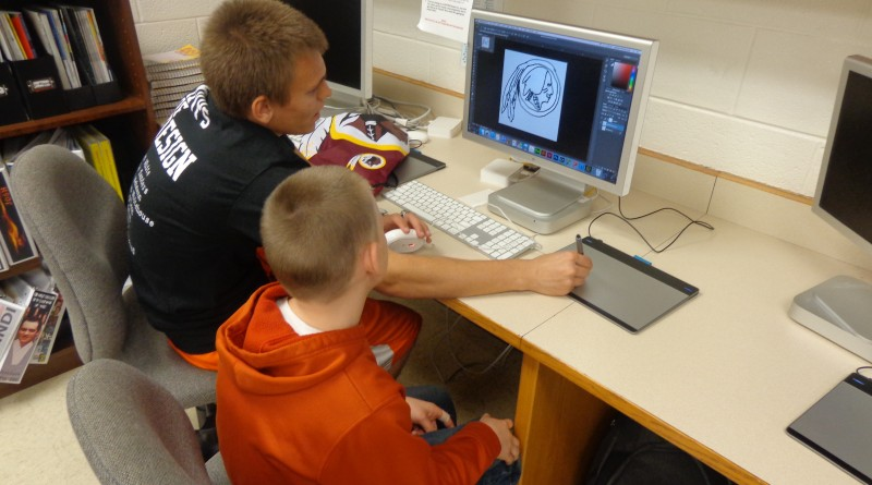 Monroe Technology Center Graphics Communications II student Jackson Whitehouse helps Hillsboro fifth grader Aaron Carter design a personalized notepad using PhotoShop and InDesign. (Courtesy of Pam Smith)