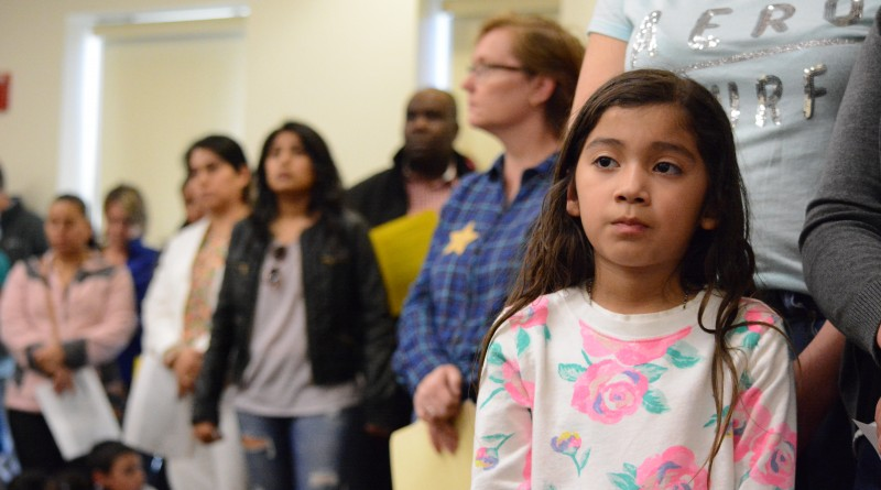 Tiffany Cruz, a second-grader, listens to the Educate Don't Segregate presentation at the Rust Library on Tuesday, March 22. (Renss Greene/Loudoun Now)