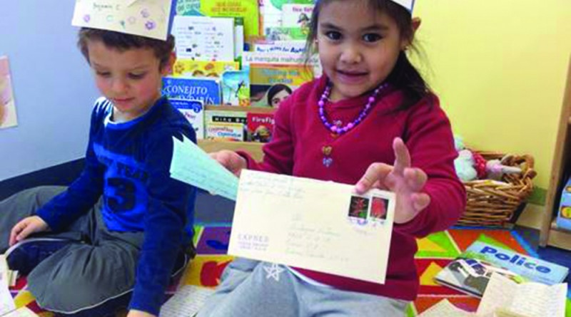 CommuniKids students Bella and Benjamin play mail carriers during a lesson on various roles in the community. (Courtesy of CommuniKids)