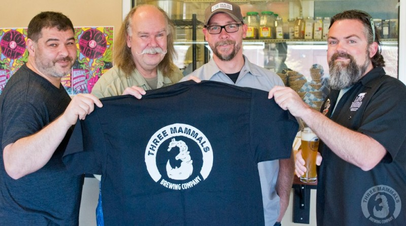 Adrien Whitman, Ocelot Brewing Company; Graham  Burns and Chris Burns, Old Ox Brewery; and Matt Hagerman, Lost Rhino, hold up a Three Mammals Brewing Company t-shirt.