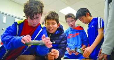 From left, Seneca Ridge Middle School students Brandon Holbert, George Egowrnov, Mikael Frey, Mathew Wang and Nehemiah Thomas use their smart phones to scan QR codes as part of an assignment in English class. (Danielle Nadler/Loudoun Now)