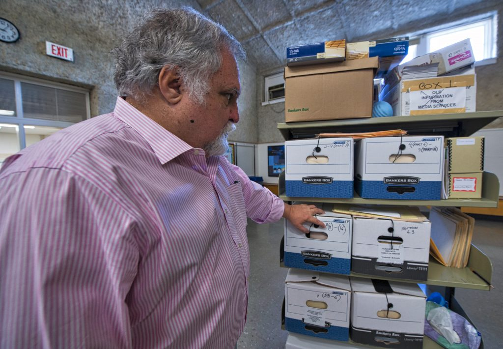 Larry Roeder with the boxes of student records from the segregation era. (Photo by Douglas Graham/Loudoun Now)