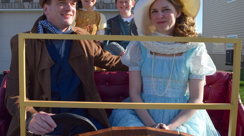 Cast members Chris Gray, as Caractacus Potts, and Jen Drake, as Truly Scrumptious, take their seats in Chitty Chitty Bang Bang with children Jemima and Jeremy, played by Caroline Jacobson and Clay Grisius.