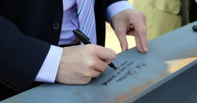 Supervisor Matthew F. Letourneau signs the last beam put in place for the Dulles South Multipurpose Center. (Courtesy of Loudoun County government)