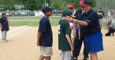 Don Rose Sr., a two-time Babe Ruth Hall of Famer and longtime Loudoun County coach, hands out awards to young players.