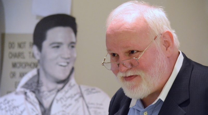 Ben Mays greets well-wishers at a reception in his honor, near a cardboard cutout of Elvis gifted to him and signed by current and former county employees and friends. Mays was known for always having Elvis pictures in his office. (Renss Greene/Loudoun Now)