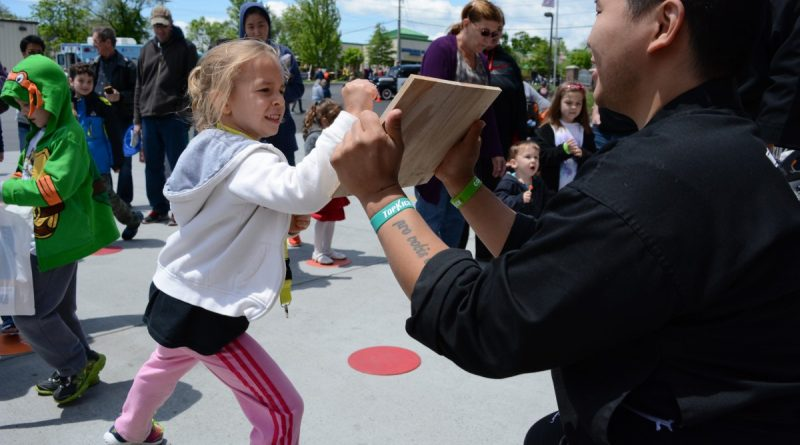 A girl tries to break a board held by a Top Kick instructor. (Renss Greene/Loudoun Now)