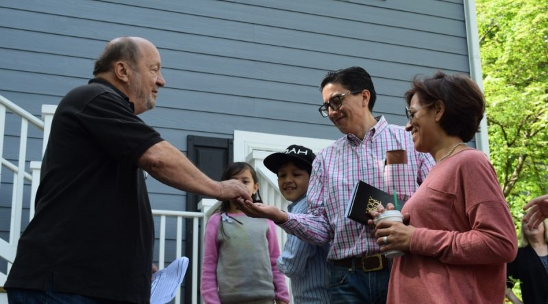 Loudoun Habitat for Humanity Construction Manager Bud Green hands the keys to a new two-story Round Hill home to Andres and Dianna Sandoval-Cadena and their three children.