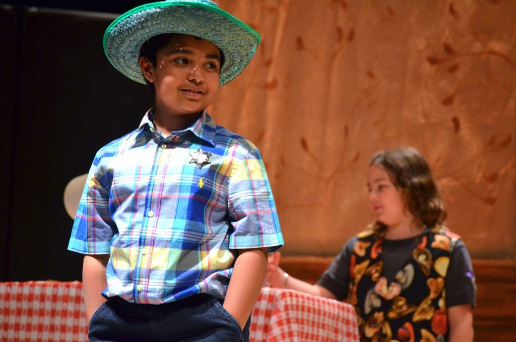 "Ashnil Dasan, as the Sherriff, performs in Drama Kids' production of ""The Cleanest Town in Texas"" on April 12. (Danielle Nadler/Loudoun Now)"