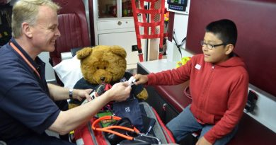 David Galen, public information officer with the Loudoun County Volunteer Rescue Squad, tests 11-year-old Angel's vital signs at Saturday's open house. (Danielle Nadler/Loudoun Now)