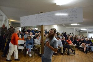 Sam Kroiz holds up a sign encouraging people to speak and donate to a legal fund before the meeting in Lovettsville. (Renss Greene/Loudoun Now)