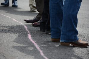 A pink chalk line marks the 200-foot boundary around the polling place inside which electioneering is illegal. Candidates and incumbents lined up with their heels on the line to greet incoming voters. (Renss Greene/Loudoun Now)