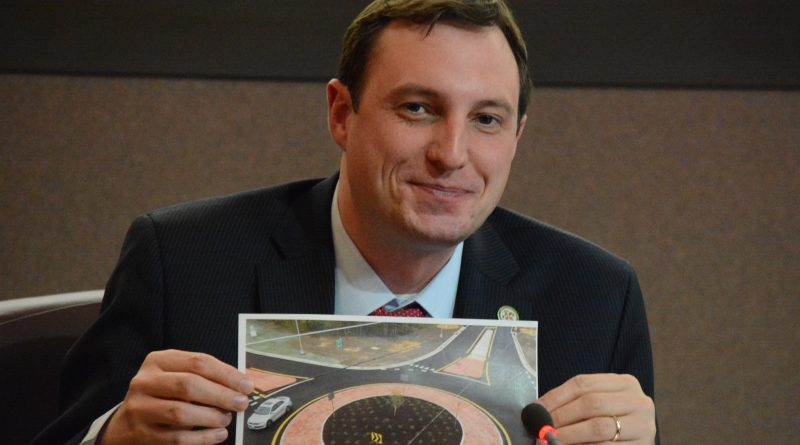 Supervisor Matthew F. Letourneau (R-Dulles) grins holding up a picture of a recently-completed roundabout inside Fairfax at an intersection that previously confounded commuters. (Renss Greene/Loudoun Now)
