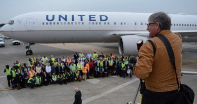 A photographer organizes United Airlines employees at Dulles Airport for a group shot in front of a United Airlines Boeing 767.  (Renss Greene/Loudoun Now)