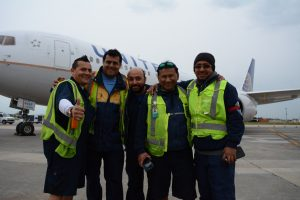 United Airlines ground crew pose for a picture in front of one of the aircraft they help keep aloft. (Renss Greene/Loudoun Now)
