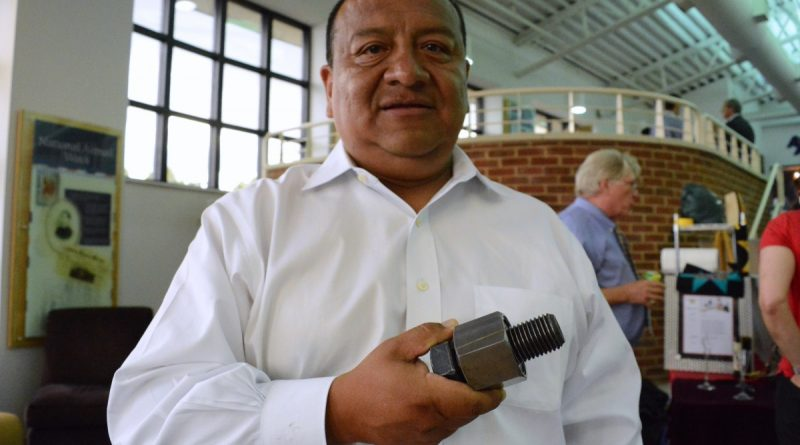 Joe Travez holds a type of fastener developed for astronauts by his company, Prototype Productions, in Ashburn. (Renss Greene/Loudoun Now)