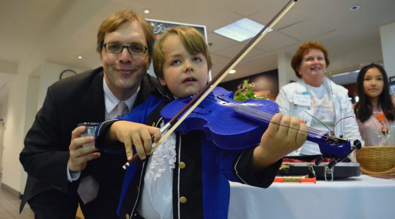 Carolina Philharmonic Artistic Director David Michael Wolff with Linton Hall School fife player Roy Wulf, demonstrating a 3-D printed violin. (Renss Greene/Loudoun Now)