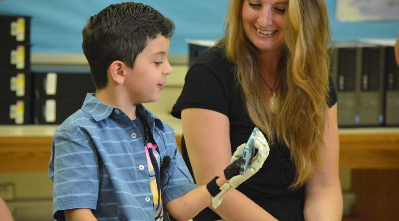 Lucas Filippini shows off his new prosthetic hand, created by his brother. (Pariss Briggs/Loudoun Moment)