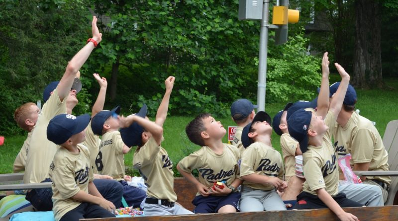 Little Leaguers wave take a break from throwing candy to wave to a drone during the Hamilton Day Parade. (Danielle Nadler/Loudoun Now)