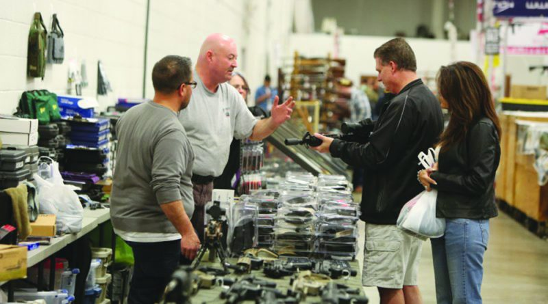 Shoppers browse at a gun show in Chantilly. As of Friday, a State Police representative will attend every gun show in Virginia to perform voluntary background checks.  [Ali Khaligh/Loudoun Now]