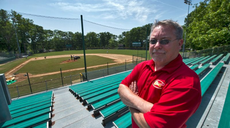 Purcellville Cannons head coach Brett Fuller poses in the stands of Fireman's Field, the team's new home field. The baseball team is a labor of love for the Fuller family.   [Douglas Graham/Loudoun Now]