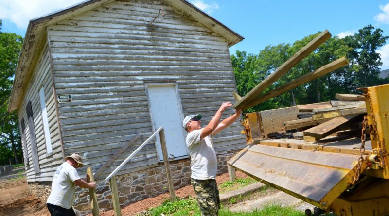 David Ratcliff and Donald Reno, of Ratcliff's Masonry, clean up the site of the former Ashburn Colored School on Ashburn Road Saturday. They restored the one-room schoolhouse's stone and lime mortar foundation and installed a new chimney stem. (Danielle Nadler/Loudoun Now)