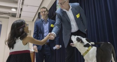 Kris Kiser, president and CEO of the Outdoor Power Equipment Institute; Casey Mindlin, regional director for Scholastic National Partnerships; and Lucky, the rescue dog who inspired the TurfMutt cartoon character, congratulate Belmont Station Elementary student Kashvi Ramani. (Photo by OPEI)