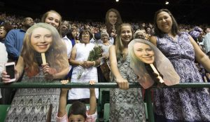 Family and friends of Stone Bridge graduating senior Kasey Brill hold up photos of her face. (Photo by Douglas Graham/Loudoun Now)