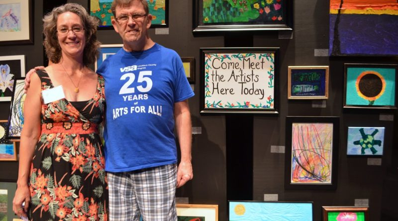Lisa Zimmer-Chu, director of visual arts at VSA Arts of Loudoun, poses with one of the organization's artists, Tim Peterson. (Danielle Nadler/Loudoun Now)