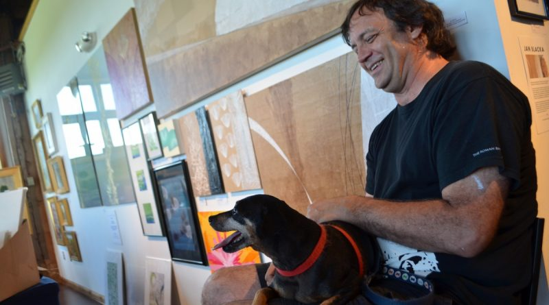 Craig Green, of Hamilton, and his pup help man the booth of his wife, artist Jan Blacka. (Danielle Nadler/Loudoun Now)