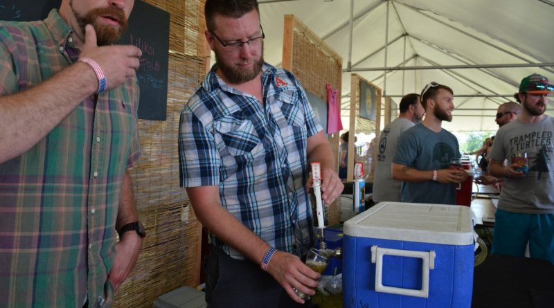Chris Banich, from Boulder, Colorado-based Avery Brewing Company, pours cold beer. (Renss Greene/Loudoun Now)