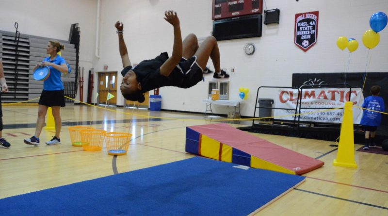 Lasana Higgins, an instuctor at More Than Cheer in Ashburn, shows off with a flip.