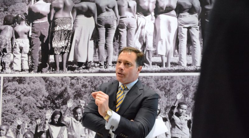 K2M founder, president and CEO Eric Major leads a tour by a mural of children in Ghana, before and after their spinal deformities were corrected with K2M technology. (Renss Greene/Loudoun Now)