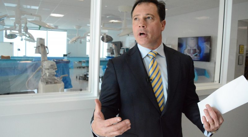 K2M founder, president and CEO Eric Major gives a tour in front of mock operating tables where doctors learn to use K2M technology. (Renss Greene/Loudoun Now)