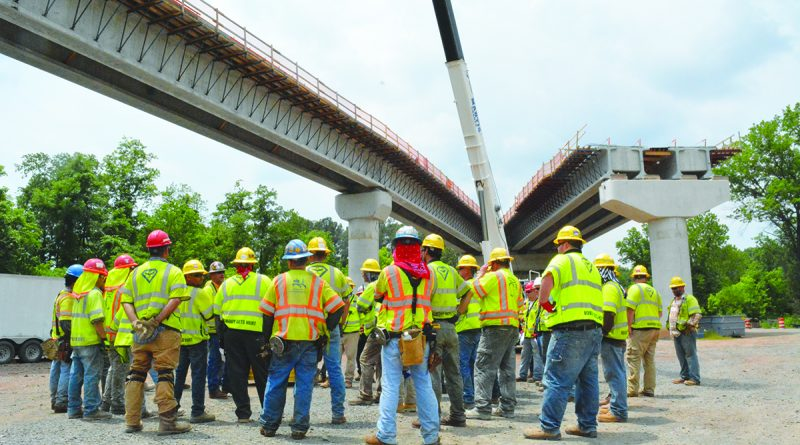 Capital Rail Constructors crew gather for a safety briefing under elevated guideway that provides access to a new rail yard under construction at Dulles Airport.  [Renss Greene/Loudoun Now]
