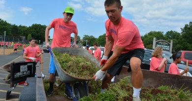 Some of the older, bigger campers load grass and dirt onto a truck. (Renss Greene/Loudoun Now)